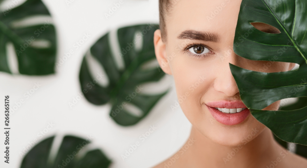 Fototapety, obrazy: Young Woman With Perfect Skin Covering Half Of Face With Leaf
