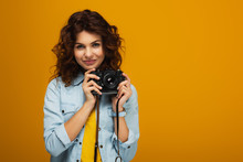 Curly Redhead Photographer Holding Digital Camera Isolated On Orange