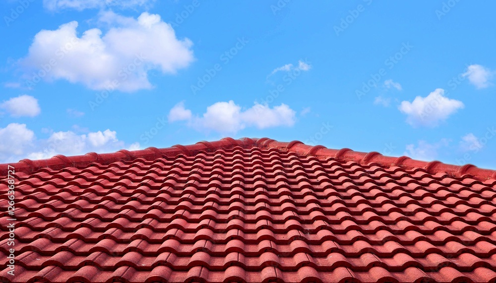 Fototapeta The old red tiles roof slope in pyramid shaped against white clouds and blue sky