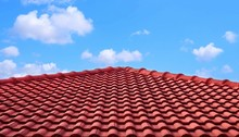 The Old Red Tiles Roof Slope In Pyramid Shaped Against White Clouds And Blue Sky