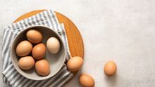 Brown And White Eggs In A Bowl On A Textured Grey Background With Copyspace.
