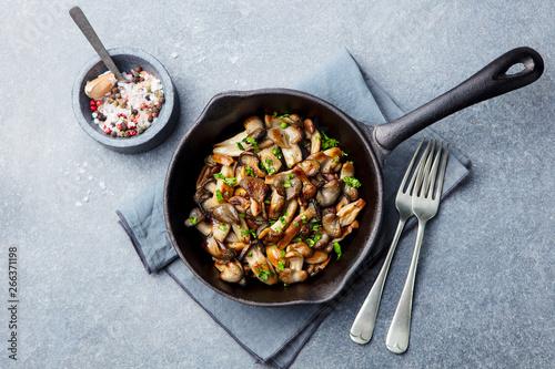 Fototapeta Fried mushrooms with fresh herbs in black cast iron pan