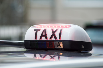 closeup of taxi sign on car parked in the street