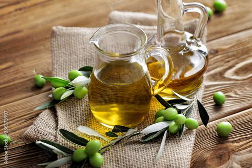 Fototapeta olive oil bottles and green olives on wooden background obraz