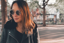 Portrait Of Asian Woman Wearing Sunglasses On The Street Around Trees