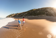 Two Kids Running By The Ocean On A Beach In New Zealand