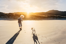 Child And Puppy Running On A Beach Together At Sunset
