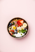 Oat Granola With Fresh Berries, Banana, Yogurt, Maple Syrup, Seeds And Mint Leaves