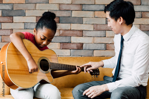 Young Asian male teacher giving a guitar lesson and teaching how to play guitar Fototapet