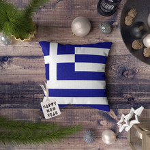 Happy New Year Tag With Greece Flag On Pillow. Christmas Decoration Concept On Wooden Table With Lovely Objects.