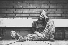 Homeless Man, Homeless Man Drug And Alcohol Addict Sitting Alone And Depressed On The Street Leaning Against A Red Brick Building Wall Feeling Anxious And Lonely, Social Documentary Concept