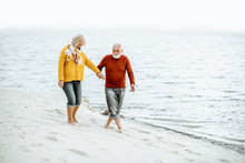 Lovely Senior Couple Dressed In Colorful Sweaters Walking On The Sandy Beach, Enjoying Free Time During Retirement Near The Sea
