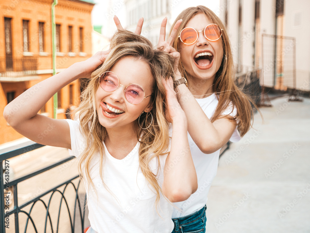 Fototapety, obrazy: Two young beautiful blond smiling hipster girls in trendy summer white clothes. Sexy carefree women posing on street background.Positive models having fun in sunglasses.Using fingers as bunny ears
