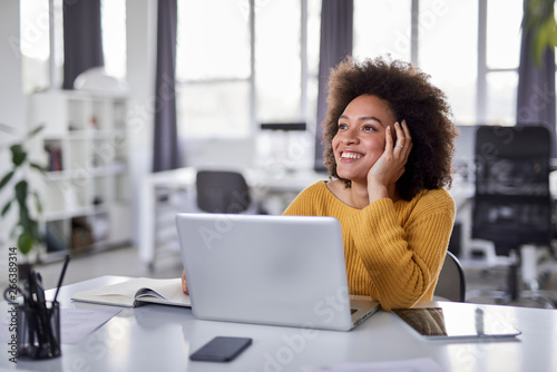 Fotomural  Cute mixed race businesswoman dressed  casual thinking how to solve a problem while sitting in modern office