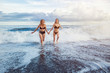 Two girls run from the ocean