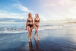 Two girls on the beach out of the water