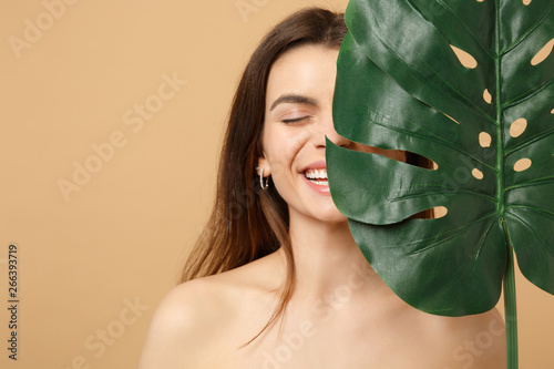 Obraz Close up brunette half naked woman 20s with perfect skin, nude make up palm leaf isolated on beige pastel wall background, studio portrait. Health care cosmetic procedures concept. Mock up copy space. - fototapety do salonu