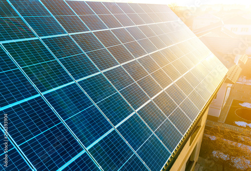 Fototapeta Close-up surface of lit by sun blue shiny solar photo voltaic panels. System producing renewable clean energy. Renewable ecological green energy production concept. obraz