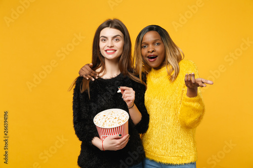 Two women friends european and african american in black yellow clothes hold bucket of popcorn isolated on bright orange wall background, studio portrait Slika na platnu