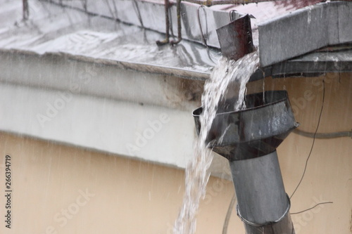 Photo Heavy rainfall, rainwater from the roof overflows through the drainpipe
