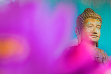 Stone Carved Statue Of Buddha Surrounded With Colorful Flowers