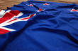 Flag of New Zealand on a wooden desk background. Silk Kiwi flag top view.
