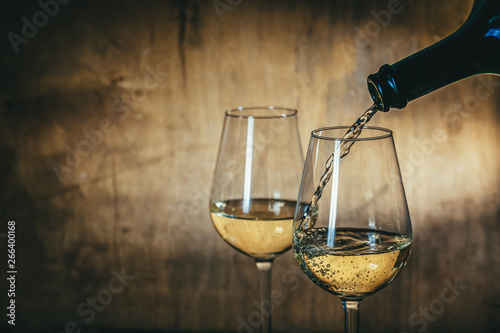 Fototapeta White wine in glasses on rustic background, copy space obraz