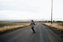 Girl Skating On Open Road