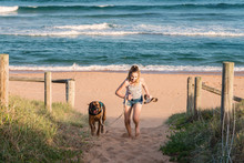 Teen Taking Her Dog For A Walk On The Beach