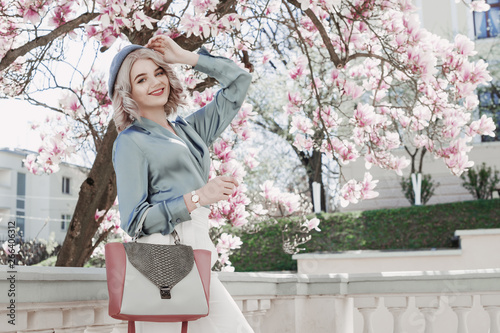 Outdoor fashion portrait of young beautiful happy smiling lady wearing  stylish white wrist watch, blue beret, blouse, holding handbag, posing in street with blooming magnolia tree. Copy, empty space