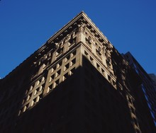 A Low Angle View Of A City Building With Sharp, Contrasting Shadows On It's Sides