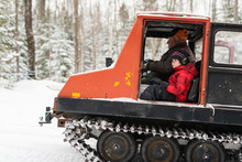 Young Boy And Old Man In Winter Muskoka Snowy Forest Riding In Vintage Snow Groomer