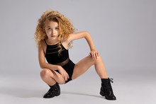 Beautiful Little Girl Gymnast In A Black Sports Swimsuit And Boots On A Gray Background.