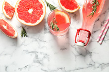 Flat Lay Composition With Grapefruits, Glass Of Cocktail And Bottle On Marble Background. Space For Text