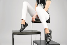 Woman In Stylish Shoes With Stands On Grey Background, Closeup