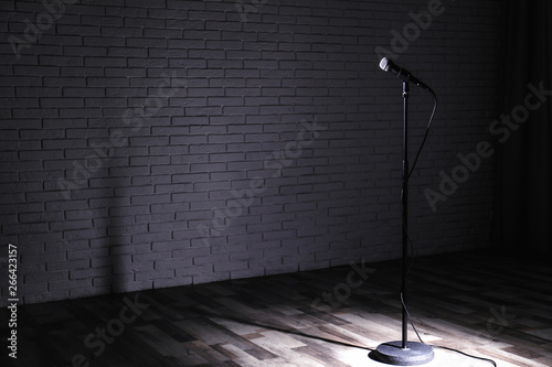 Fototapeta  Microphone on dark stage near brick wall. Space for text