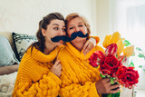 Senior mother and her adult daughter taking selfie with flowers using photo booth props at home. Mother's day concept. - 266424593