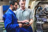 Arbeiter besprechen ein Projekt vor einer CNC Drehmaschine