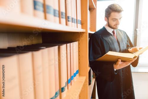 Cadres-photo bureau Individuel Rechtsanwalt mit Robe will zu Gericht, liest lieber noch einmal nach