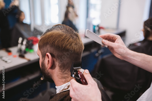 Close up shot of man getting trendy haircut at barber shop. Male hairstylist serving client, making haircut using machine and comb