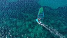 Aerial Top View Photo Of Fit Man Practising Wind Surfing In Exotic Open Ocean Bay With Crystal Clear Emerald Sea