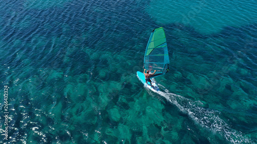 Foto  Aerial top view photo of fit man practising wind surfing in exotic open ocean ba