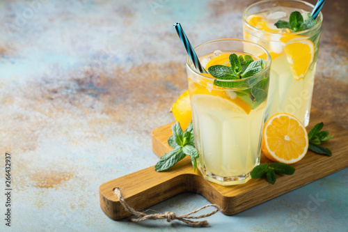 Two glass with lemonade or mojito cocktail with lemon and mint, cold refreshing drink or beverage with ice on rustic blue background Wallpaper Mural