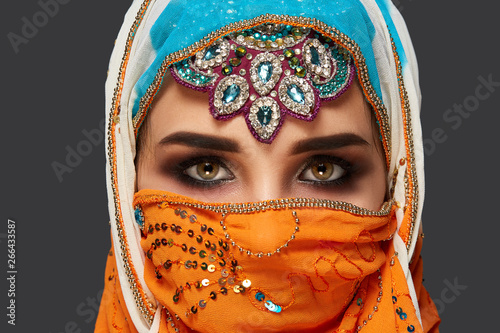 Fototapeta Studio shot of a chrming female wearing the colorful hijab decorated with sequins and jewelry. Arabic style. obraz