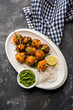 Tandoori aloo are roasted potatoes with Indian spices. It's a party appetiser served with green chutney. selective focus