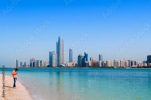 Tourists on beach at marina island with modern Abu Dhabi skyline cityscape