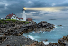 Lighthouse Beam Light In Stormy Clouds. Portland Head Light, Maine, USA.