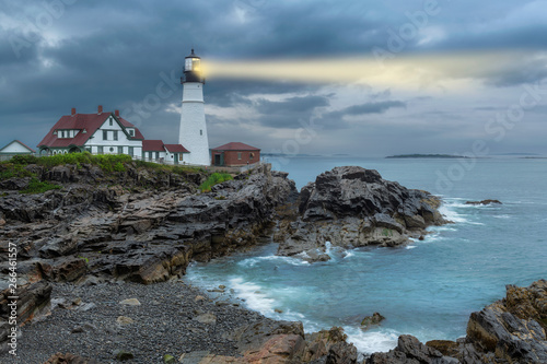 Garden Poster Lighthouse beam light in stormy clouds. Portland Head Light, Maine, USA.