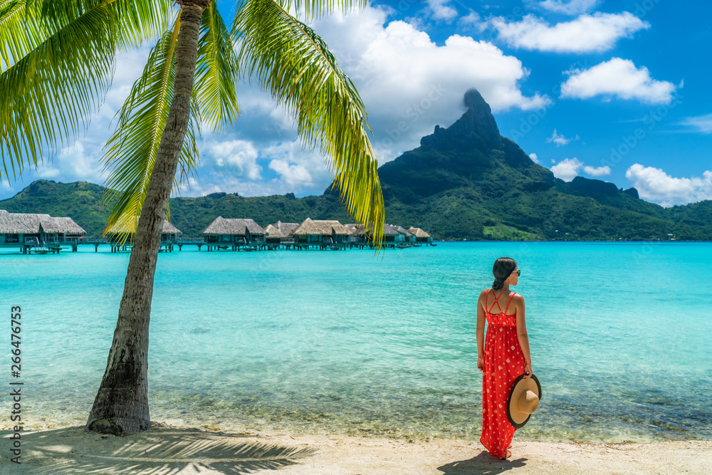 Fototapeta Bora Bora luxury hotel vacation tourist woman relaxing by ocean beach with view of Mt Otemanu in Tahiti, Frenc Polynesia. High End resort with overwater bungalows villas.