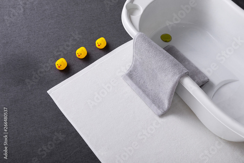Obraz White bathtub and bath mat on a gray background, grey towel on the side - fototapety do salonu